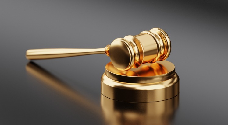 Golden gavel resting on a golden base surrounded by a reflective gray background.